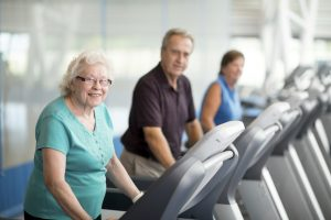 Senior adults at the gym walking on a treadmill